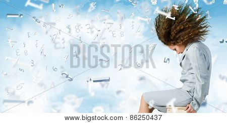 Young businesswoman with waving hair sitting on chair