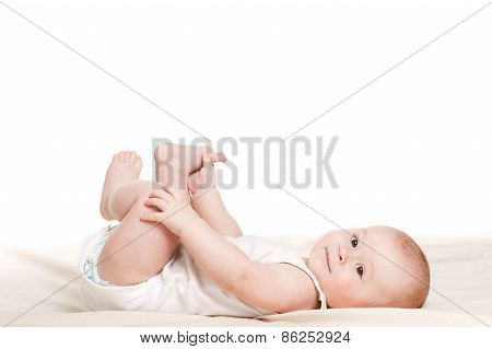 Charming little girl lying on the bed, on a white background.