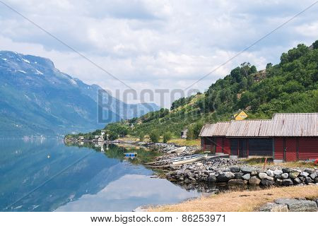 Red boat-houses at th shore of fjord