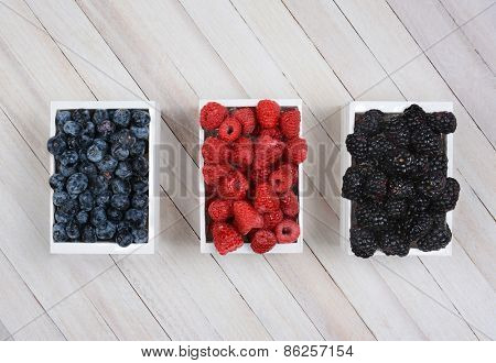 Three mini wood crates of berrie on a rustic wood surface. Blueberries Raspberries and Blackberries in small white boxes shot from a high angle.