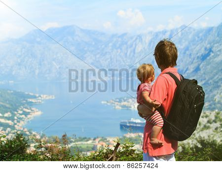 father with little daughter looking at mountains