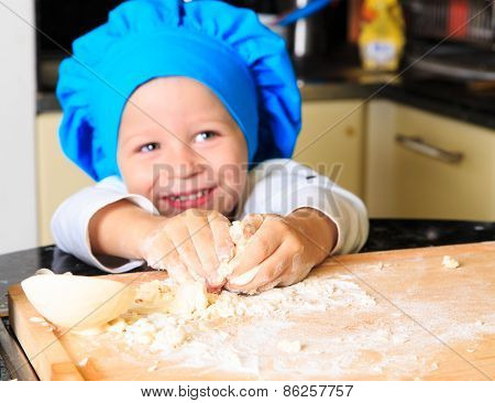 happy little boy kneading dough