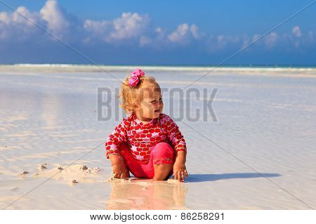 cute little girl playing on summer beach