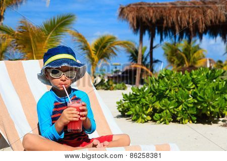 cute little boy drinking juice on the beach
