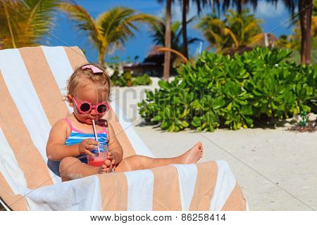 cute little girl drinking juice on the beach