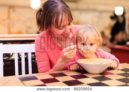 mother and little baby eating in restaurant