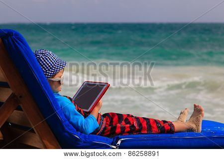 little boy with touch pad at the beach