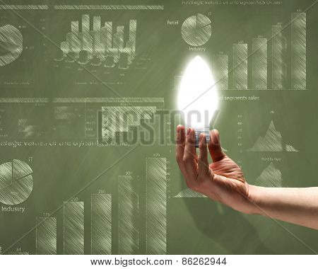 Close up of hand holding light bulb with sketches at background