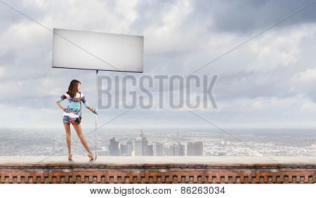 Rear view of young attractive woman with blank white banner