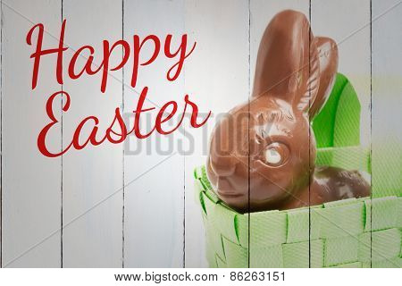 happy easter against chocolate bunny in a basket