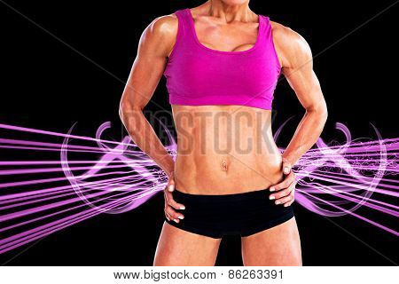 Female bodybuilder posing with hands on hips mid section against purple design