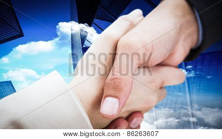 Close up on new partners shaking hands against skyscraper