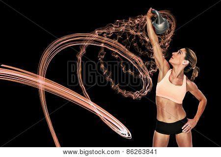 Female blonde crossfitter lifting kettlebell above head against purple design