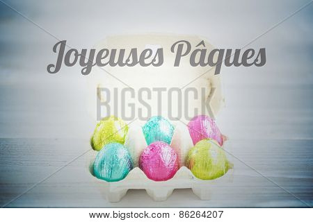 joyeuses paques against carton with easter eggs