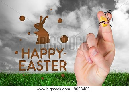 Fingers as easter bunny against green grass under grey sky