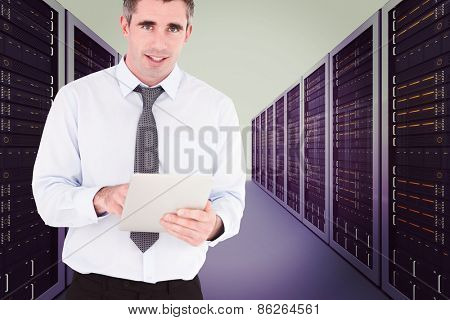 Portrait of a businessman with a tablet computer against server hallway