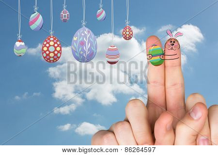 Fingers as easter bunny against cloudy sky