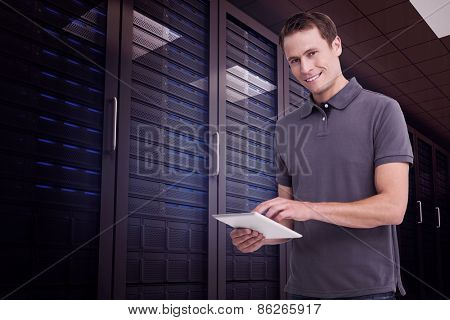 Smiling young man with tablet computer against digitally generated server room with towers