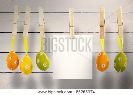 hanging easter eggs against painted blue wooden planks