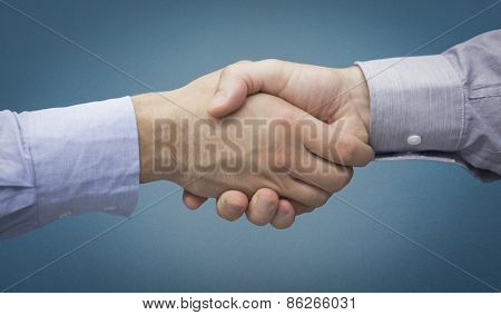 Hand shake in front of wires against blue