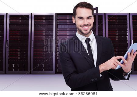 Businessman using his tablet while looking at the camera against server towers