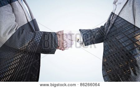 Close up on two businesspeople shaking hands against skyscraper