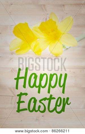 happy easter against pair of pretty yellow daffodils with copy space