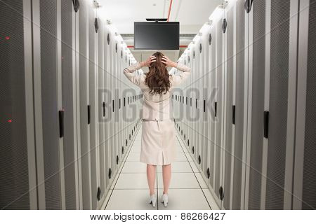 Businesswoman with hands on head standing back to camera against data center