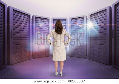 Businesswoman standing back to camera against server room with towers