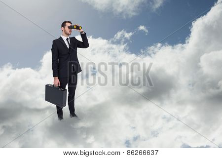 Businessman holding a briefcase while using binoculars against blue sky with clouds