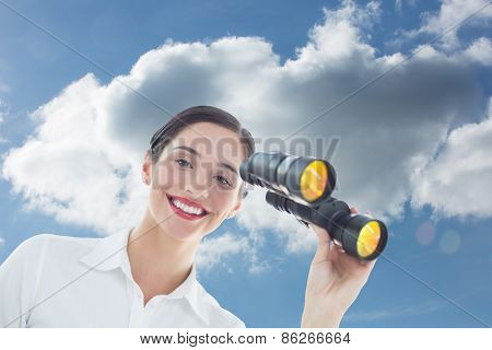 Smiling business woman with binoculars against cloudy sky