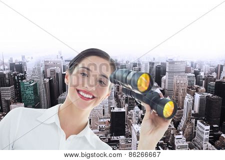 Smiling business woman with binoculars against high angle view of city