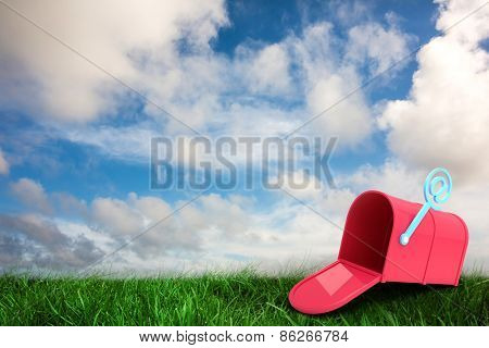 Red email post box against green grass under blue sky