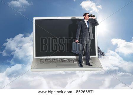Businessman looking through binoculars against mountain peak through the clouds