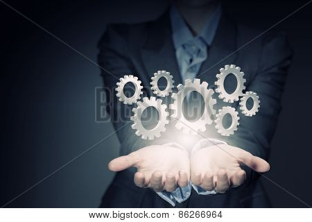 Close up of businesswoman holding gears in hand