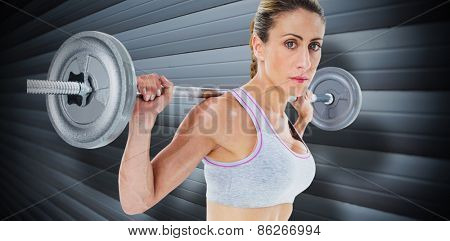 Strong female crossfitter lifting barbell behind head looking at camera against grey shutters