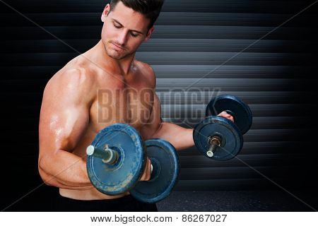 Bodybuilder lifting dumbbell against black background