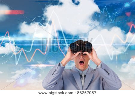 Suprised businessman looking through binoculars against stocks and shares on black background