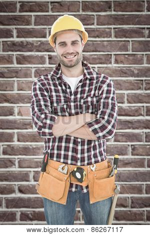 Confident male handyman wearing tool belt against red brick wall