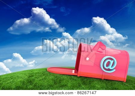 Red email post box against green field under blue sky
