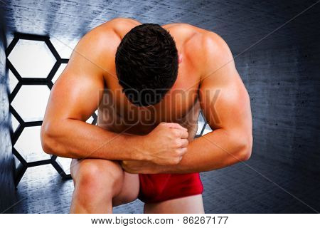 Bodybuilder posing against hexagon room