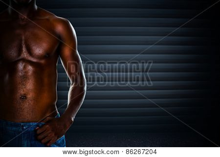 Close-up mid section of a shirtless muscular man against black background