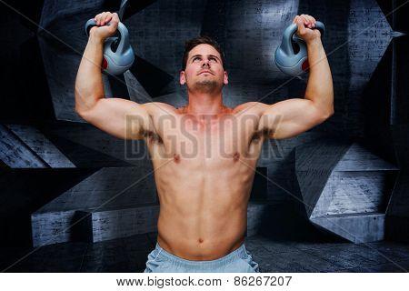 Bodybuilder holding kettlebells against dark room