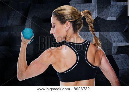 Female bodybuilder holding a dumbbell against dark room