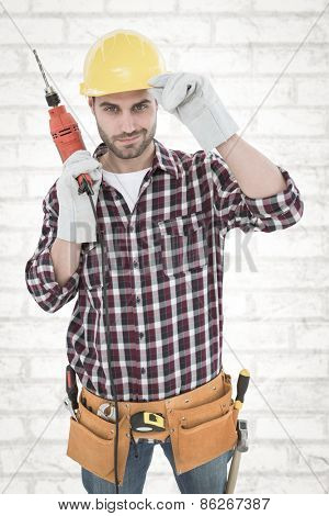 Confident handyman holding drill machine against white wall