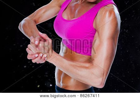 Female bodybuilder flexing mid section against black background