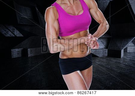 Female bodybuilder flexing in sports bra and shorts against dark room