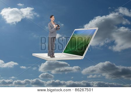 Curious young businesswoman with binoculars against sky and clouds