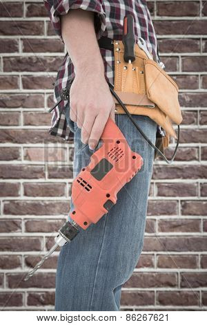 Male handyman holding drill machine against red brick wall