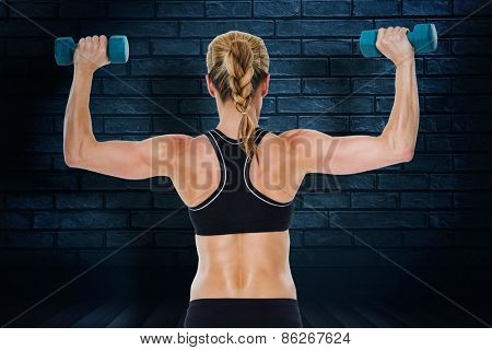 Female bodybuilder holding two dumbbells with arms up against black background